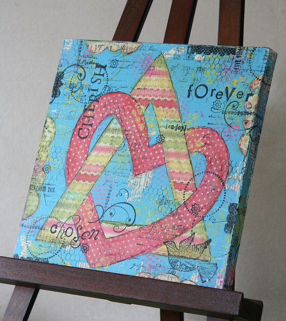 The symbol of the heart with the triangle is an adoption symbol . . . the three sides of the triangle represent the adoptive family, their children, and the birth families. Those 3 things have created this family and they are all linked by a heart (love).  beautiful adoption art-mixed media canvas art by mama's artsy treasures