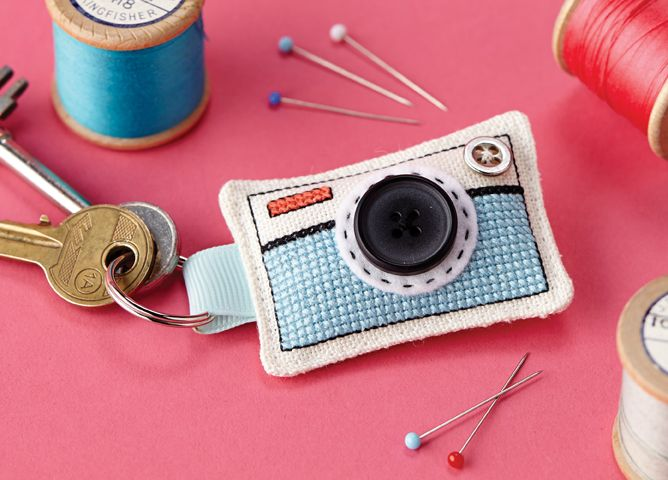 Camera keyring combining cross stitch and sewing. Includes a button lens!