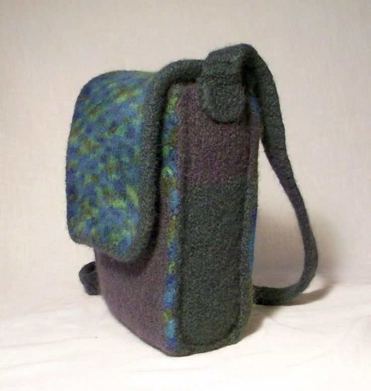 This useful felt bag has crisp shaping with contrast edging and an interesting layered edge seam feature. The internal pocket is an ideal size to keep your I pad/notebook or similar sized device safe and secure. The front pocket and large main compartment will hold all your other essential items. The flap secures with 2 magnetic closures or buttons and the strap will fit neatly over your shoulder.This bag is knitted first in pure wool and then felted in an ordinary washing machine.