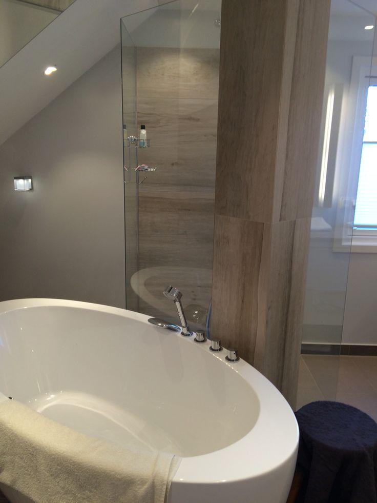 Gulvstående badekar med glassdusjen på baksiden. Søyle fra gulv til tak med armatur påmontert