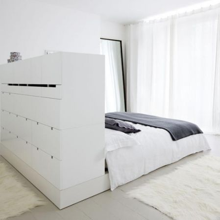 Headboard, room divider and storage in one to create a dressing area in a bedroom.