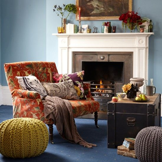 Eclectic living room  A formal small sofa with turned legs and castors gets a makeover with a velvet cover depicting woodland creatures. Provide extra seating with chunky knitted pouffes, and complete with a regal blue carpet.