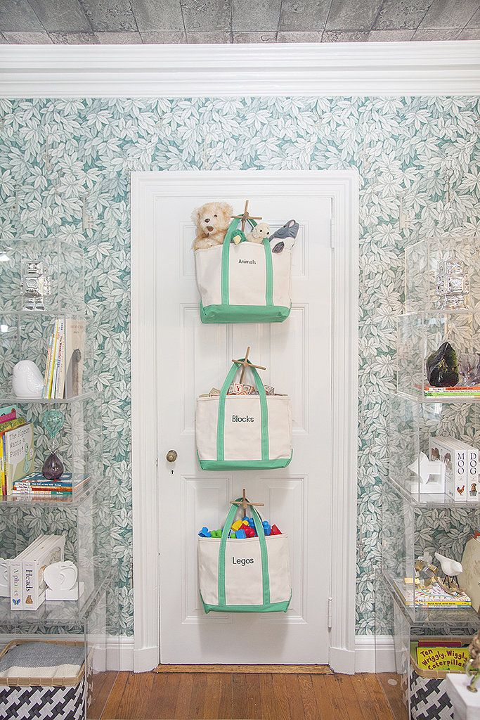 """""""You can never have too much storage in a nursery,"""" Lisa says. """"Babies just have a lot of stuff. While people usually gravitate toward floor bins and bookcases, they don't often think of taking advantage of other vertical surfaces in the room — like doors. Here, I installed three hooks on the back of the door and hung embroidered boat totes that I ordered from Lands' End. It's easy. Baby wants to play with something? Take down the bag. Baby is done playing with something? Load up the bag and…"""
