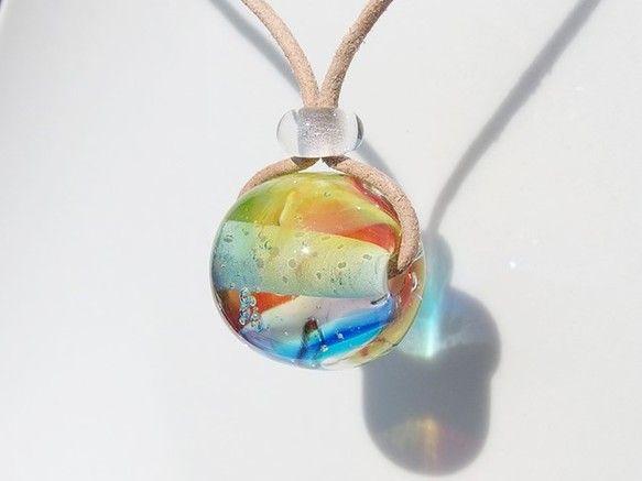 虹色を閉じ込めたガラスは虹やオーロラ、まるで宇宙の様♪バーナーワークで一つ一つ心を込めてガラスに虹色と泡を混ぜ込み作ります(*^^*)光りが当たると泡で屈折してキラキラ綺麗☆彡トップをクルクル回すと雰囲気が変わりまるで虹色宇宙の様な、コロンとまん丸ガラスネックレスです♪長さはガラス玉の位置を変えるだけの簡単調節! 調整のガラス玉も全部手作りです。 -------------------※金属不使用(金属フリー)の作品です。金属アレルギーの方も安心してお使いください。-------------------◆◇◆たくさんのご注文ありがとうございます(*^^*)◆◇◆ ◆◇◆この作品は完全受注制作となっております◆◇◆ ※制作にお時間頂きます※※こちらは特に長め10日ほどお時間いただきます※-------------------■ネックレス長さ: 約80cm調整可 ■ネックレス素材: 皮 (滑らかで柔らかい高品質な鹿皮を使用しています)■トップ大きさ: 約2cm ■トップ素材: ガラス(ベネチアンガラスを使用しています)…