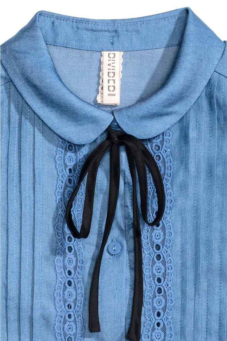 Блузка без рукавов: Тканая блузка без рукавов. На блузке круглый воротник с завязками, а также складки и кружевные вставки спереди.