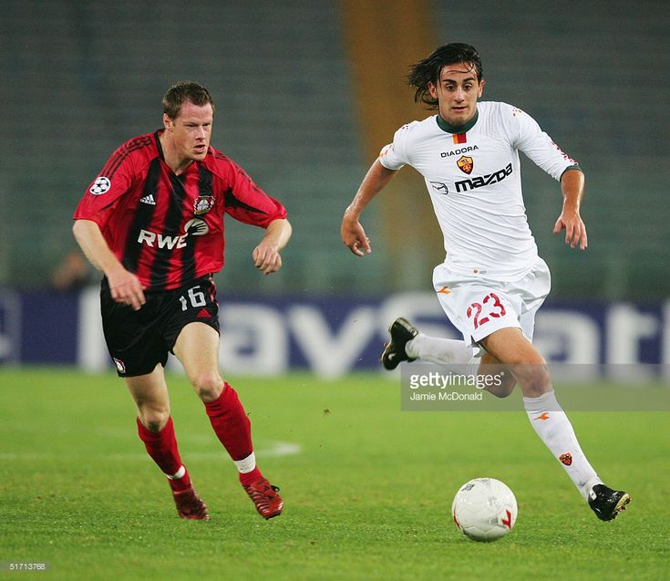 Alberto Aquilani of Roma is pursued by Jacek Krzyn?wek of Leverkusen during the UEFA Champions League, Group B match between AS Roma and Leverkusen at The Olympic Stadium on November 3, 2004 in Rome, Italy.