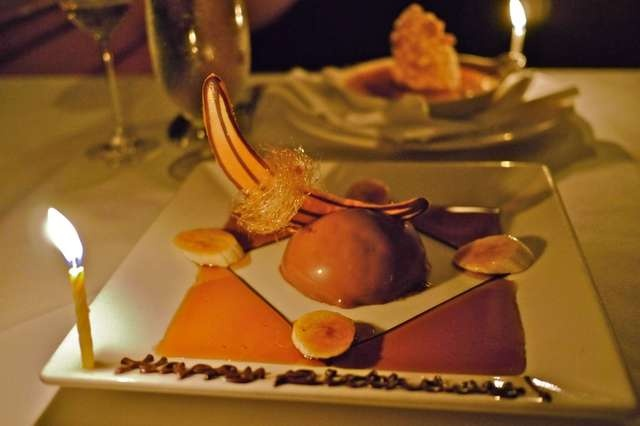 Creamy banana pudding covered by a dome of chocolate ganache and garnished with a banana-shaped tuile. Triangles of hardened caramel, accented with slices of banana, frame the pudding. From the Peninsula Grill in Charleston.