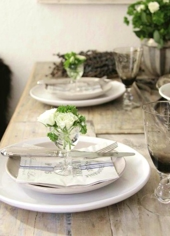 neutral and white place setting on wood table. smokey grey glasses