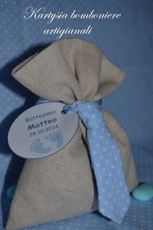 Sacchetto/segnaposto per battesimo in cotone naturale, chiuso da una piccola cravatta azzurra con pois bianchi. Interamente realizzato a mano.