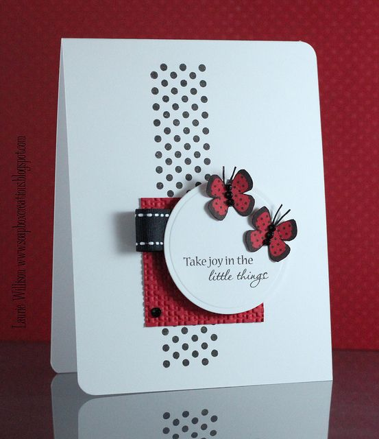 card by Laurie Willison. I like the layout with the diecut area behind focal point. Good mix of white, black and red in unequal quantities and the main circle is a good example of repetition of the circular die cut area but in on a larger scale.