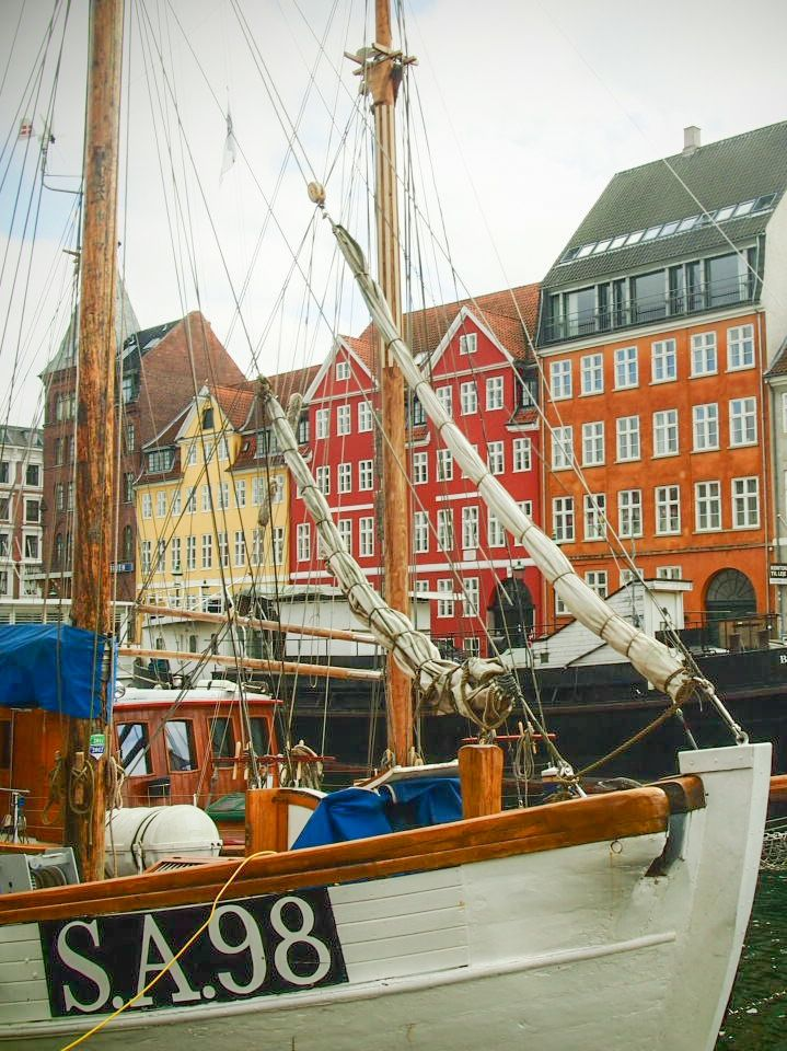 Sailboat and beautiful houses in Nyhavn, Copenhagen, Denmark.