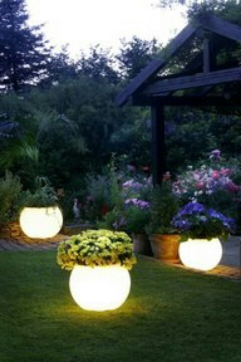 Paint pots with glow paint. They absorb sunlight during the day and glow at night.