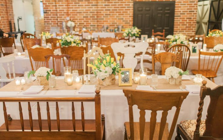 farm tables with mismatched vintage chairs fill the farmer's market. the tables are dressed with burlap runners, white and yellow flower arrangements in mercury glass and birch wood containers and candles of varying heights.
