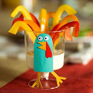 Face out of card stock. With marker, add pupils to paper eyes made by a hole punch. Assemble the turkey, then glue it to the side of a stemmed plastic cup. Put a few dollops of vegetable dip in the cup and add slices of bell peppers.