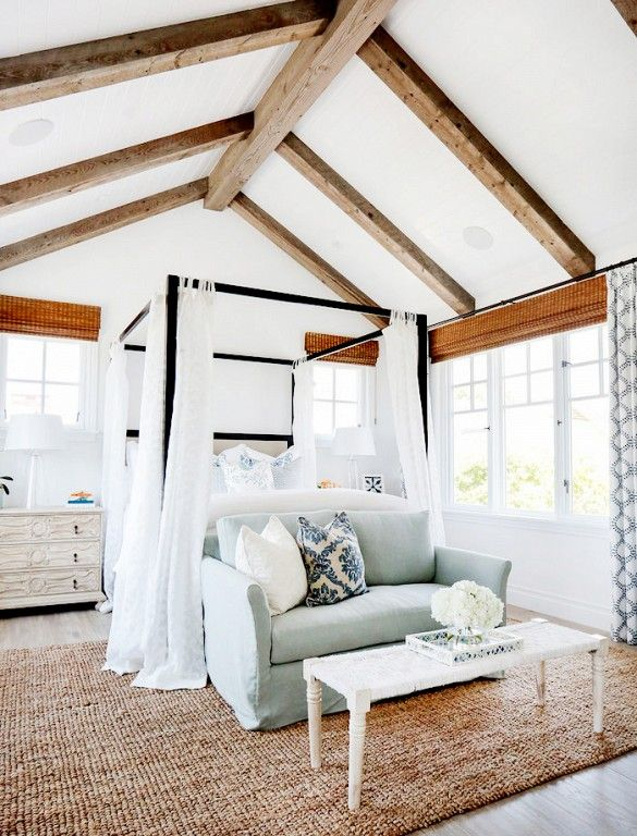 Bedroom with vaulted ceilings, exposed wood beams, black canopy bed, light blue sofa, and white furnishings including nightstands, lamps, and coffee table.: