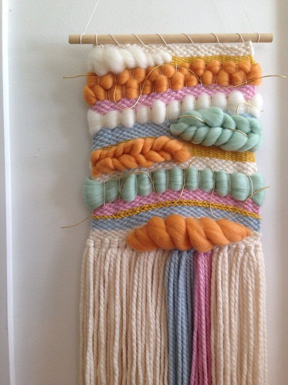 Handmade woven wall art/ woven wall hanging handwoven on a lap loom using wool roving and wool yarn. Colors include ivory, bright pink, light blue,