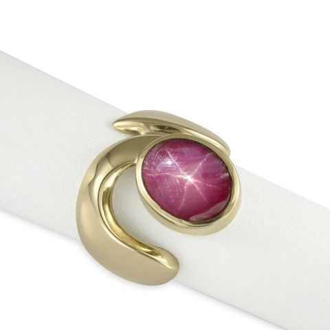 JENS HANSEN Beautifully simple, this keyhole design in 9ct Yellow Gold is set with a smooth lustrous synthetic Star Ruby cabochon. The gemstone is a rich, gleaming red, and is a 12 by 10 mm oval securely set into a bezel setting. The polished band is curved, with strong fluid shapes and comfortable rounded edges.