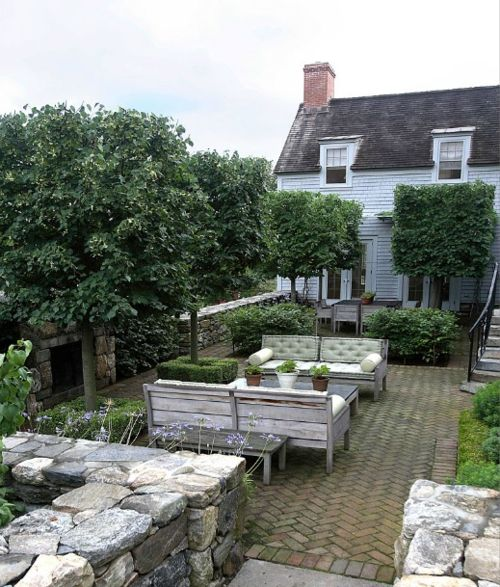 Understated and perfect patio - herringbone brick pavers, fireplace, benches with bolster pillows, clipped hedges - perhaps a koi pond - Doyle Herman Design Associates