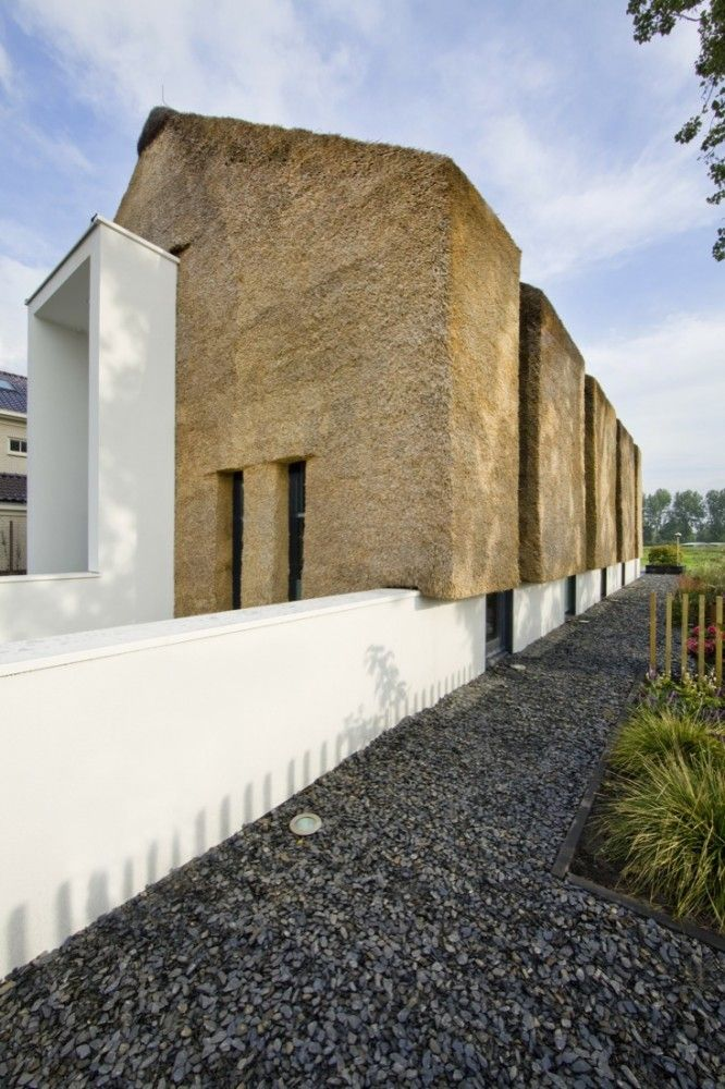 love the contrast of familiar materials on this building made of haystacks and white plaster