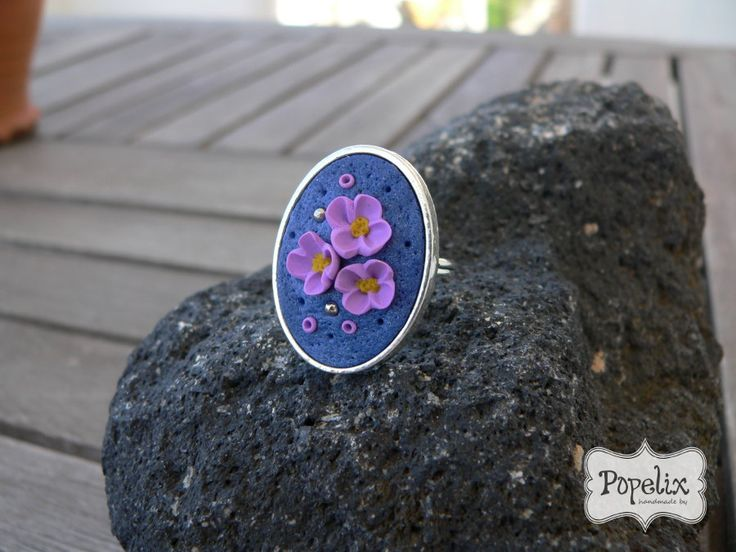Δαχτυλίδι από πολυμερικό πηλό σε καστόνι. Μοβ λουλουδάκια και μπλε φόντο. #fimo #jewelry #polyclay