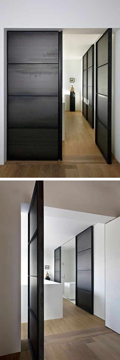 Large pivoting doors welcome you to the master bedroom and bathroom in this apartment.