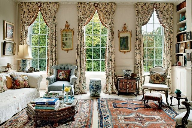 At one end of Lady Wakefield's drawing room, three tall Georgia windows frame the greenery of the garden. The full-length floral-print curtains from Colefax and Fowler add to the effect.