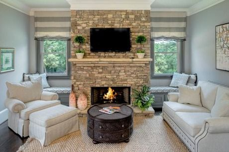 Window seats flank a stacked stone fireplace in this cozy Keeping Room. New homes in The Estates at Davis Ridge community by Traton Homes in Marietta, GA.