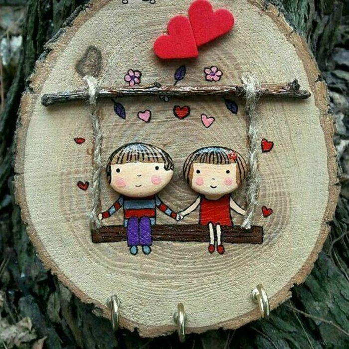 peindre des galets, un berceau avec deux enfants en galets sur un rondin de bois