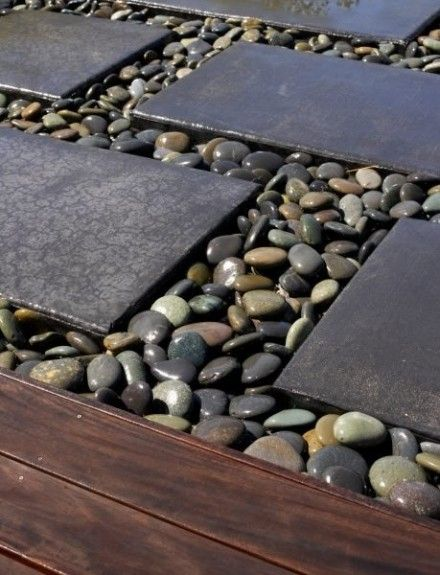 River rocks between cement stones off porch around the garden