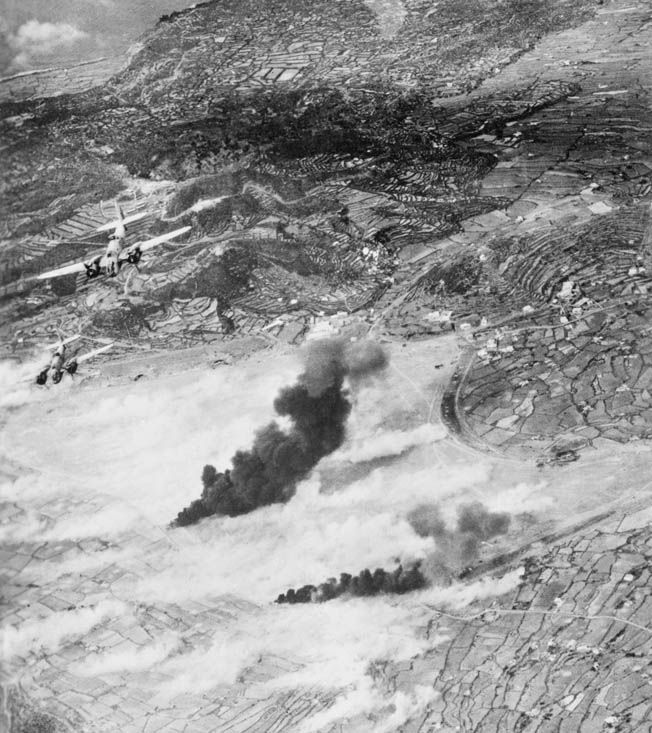 """Martin 187 """"Baltimore"""" light bombers of No. 21 Squadron, Royal South African Air Force, bank away from smoke billowing from an oil storage facility they have just bombed."""
