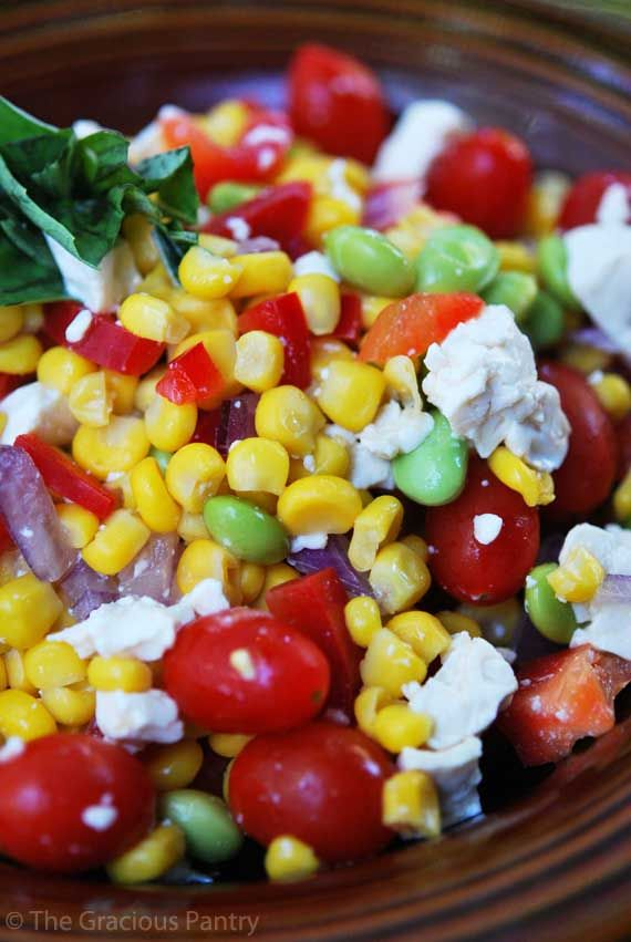 CLEAN EATING CORN SALAD (Makes 14 servings)  Salad:  2 pounds sweet corn  1 large red bell pepper  1 (10 ounce) package cherry or other small tomatoes  1/2 large red onion  1 pound package edamame beans (shelled)  1 (10 ounces) package tofu (optional)  Dressing:  4 teaspoons ground black pepper  1 teaspoon salt  4 teaspoons garlic powder  4 tablespoons olive oil  1/2 cup balsamic vinegar  1 small bunch fresh basil (about 1-2 cups depending on your tastes)