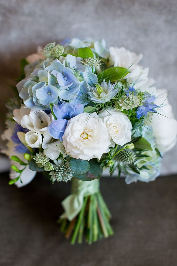Blue hydrangea, sea holly and love-in-the-mist, and white freesias and roses.