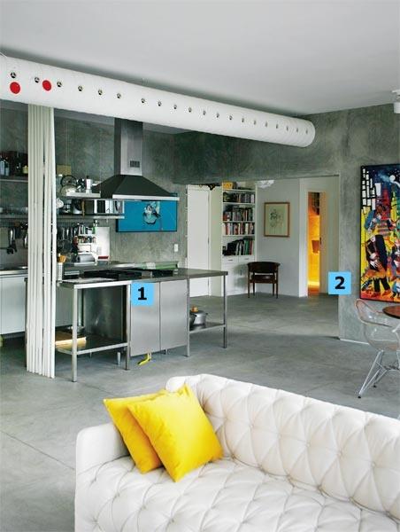 """1. Ilha na cozinha. Totalmente aberto para a sala, esse ambiente ganhou uma ilha de aço inox (projeto da Maqcem), que abriga o fogão industrial (Metalmaq). Coifa Incomar. 2. Placas de cimento. Feitas na obra, as peças que revestem a parede têm 60 x 60 cm e as do piso 1 x 1 m. """"Essa paginação modulada facilita qualquer remendo que seja necessário"""", aponta o arquiteto argentino Sebastian Gómez. O tom cinza vem da mistura de 1/3 de cimento (Nassau), areia peneirada fina e Bianco (Otto…"""
