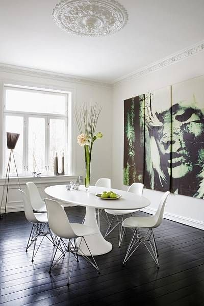White molded plastic chairs, table, walls and ceiling are lifted above the black-stained wooden floor.
