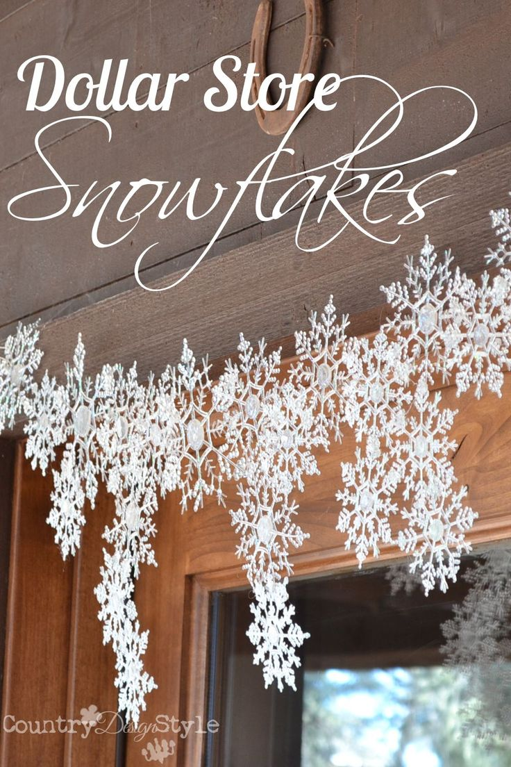 Melting snowflakes with a hot glue gun! Dollar store snowflakes hanging over our front door.  http://countrydesignstyle.com
