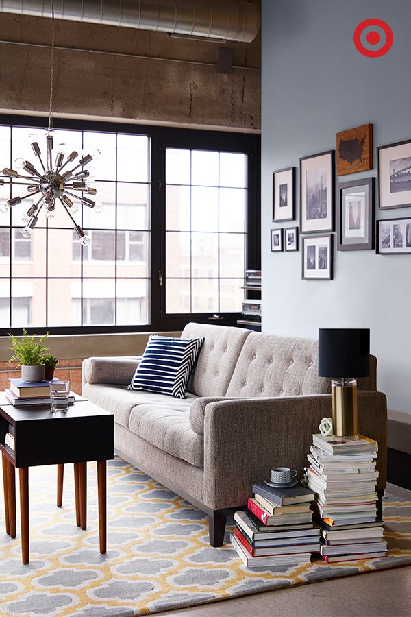 Invest in one big-ticket item per room, like this neutral, mid-century modern Armen sofa—if you love it, you'll have it forever. Add textured details, mixed metals and pops of color through throw pillows, lightings and rugs that play off of one another, and keep the space lively and warm—a perfect combo when creating a place for friends to gather. Don't forget to add personalized touches, like stacked books as an accent table.