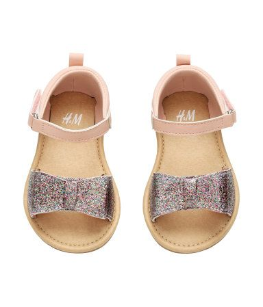 Powder pink. Sandals in imitation leather. Glittery strap over front of foot with large bow and tab with Velcro fastener at side. Imitation leather insoles
