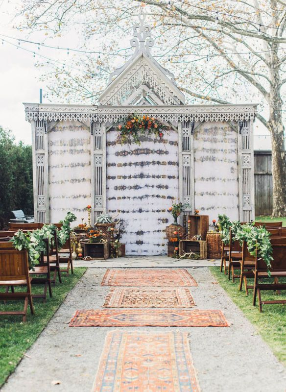 A rug-lined aisle is perfect for a fun boho wedding. We love these faded Moroccan print finds!