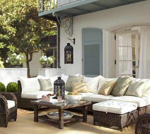 Pretty, Mediterranean style patio. Woven sectional seating, armchair and coffee table. Assorted blue pillows, woven rug and candle lantern lighting.