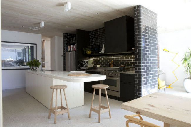 Modern kitchen by Melbourne architect Clare Cousins. It features exposed-aggregate concrete, soaped timber and dark brick to give it a unique look.