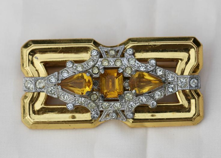 This fabulous Art Deco brooch / pin was made by a company called Rice-Weiner and dates back to the 1930s. It is set with many sparkling crystal clear and amber rhinestones. The current value for this piece varies between NZ$200 to 300. Rice-Weiner was founded in Rhode Island, USA in 1938.  Rice-Weiner produced jewellery for the famous American artist McClelland Barclay. According to several sources the McClelland Barclay signature was used from 1935 until 1943.