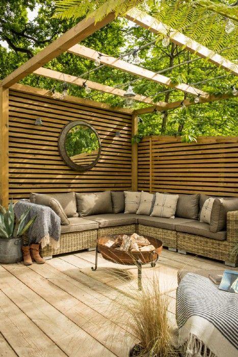Large decking area with a festoon lit pergola area and rattan corner sofa