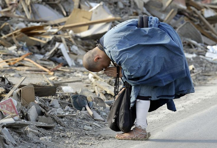 A Buddhist monk Sokan Obara, 28, from Morioka, Iwate Prefecture, prays for the victims in the debris in the area devastated by the March 11 tsunami in Ofunato, Iwate Prefecture, Japan, Thursday, April 7, 2011. Hours later another powerful earthquake hit near the devastated city of Sendai, briefly raising fears of another tsunami. 愛