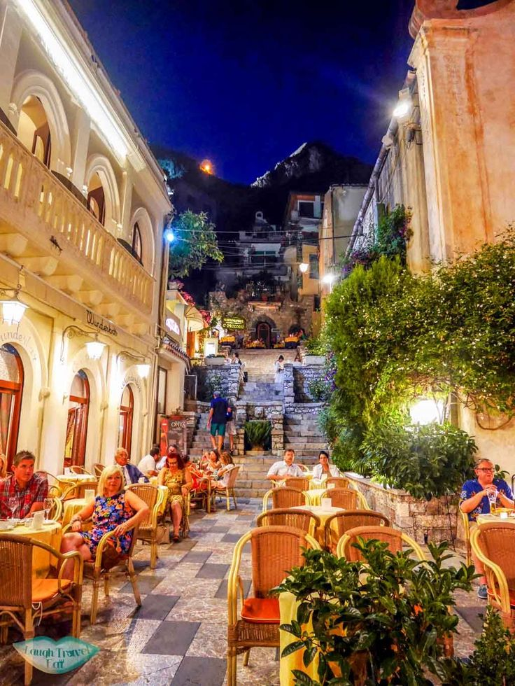 One of the many side streets in Taormina, ever so lively with restaurant tables filling up 2/3 of the street | Laugh Travel Eat