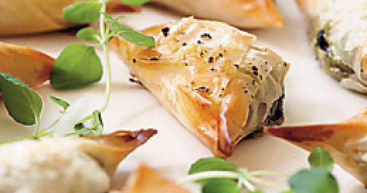 Käteensopivat feta-pinaattikolmiot ovat mainio piknikeväs tai juhlapöydän suolainen pikkuherkku! Ohuen filotaikinakuoren sisään kätkeytyy mehevä feta-pinaattitä