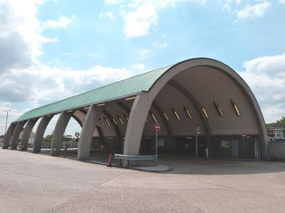 This reinforced concrete arched bus station with copper-covered barrel vault roof is at Newbury Park, London. It was designed by Oliver Hill in 1937, but building had to be postponed due to  WW2 and the bus station didn't open until 1949. The original plan was to rebuild the Underground station but this never happened.