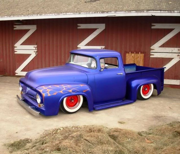 ford with a smoothed exterior chopped top and wrapped in a satin blue paint job atop wide white wall wrapped red wheels