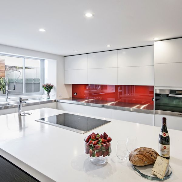 In ths kitchen – like a slick of red lipstick – this coloured glass splashback punctuates the streamlined kitchen, making the area more dynamic.