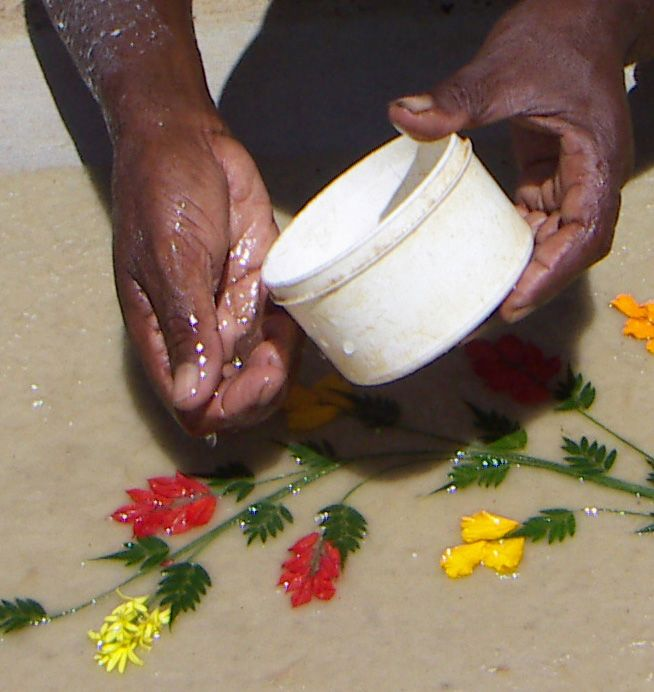 The craftsman adds some more water to make the fresh flowers get well attached to the barkpapermass. After this, the paper is dried in the sun.