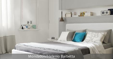 Der Trend zur grauen Farbe spiegelt sich auch in diesem Schlafzimmer wider: Kombiniert mit Weiß und mit einem türkisen Akzent als Kissen erstrahlt das Schlafzimmer in moderner Frische. Ein romantisches Element bildet die Schaukel, die zur Ablage an der Wand umfunktioniert wurde. Die hellgraue Wandverkleidung bildet mit einer kleinen Auslassung ebenfalls Gelegenheiten zum Ablegen von Büchern, Wecker und Deko und bildet einen schönen Rahmen um das Betthaupt.